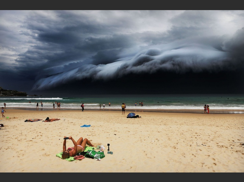 Sunbather oblivious to the ominous shelf cloud approaching –  on Bondi beach.