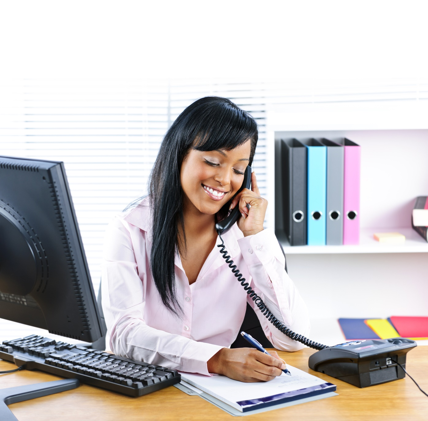 Smiling young business woman on phone taking notes in office