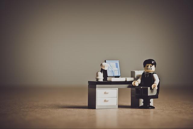 santé au travail - Lego : homme d'affaire désespéré à son bureau