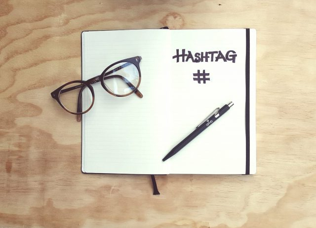 An open book with the word hashtag written on it. A pen and glasses are placed on the book